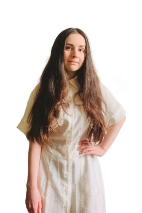 Headshot of Erin, she has one hand on her right hip and is wearing a cream dress
