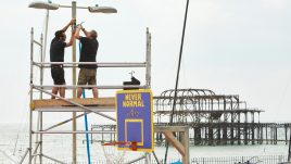 Two men on scaffolding attaching speakers to a lamp post