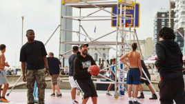 Basketball players on the court in front of scaffolding