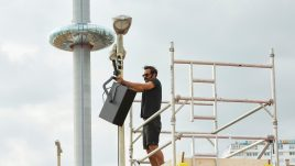 man on scaffolding attaching speakers to a lamp post