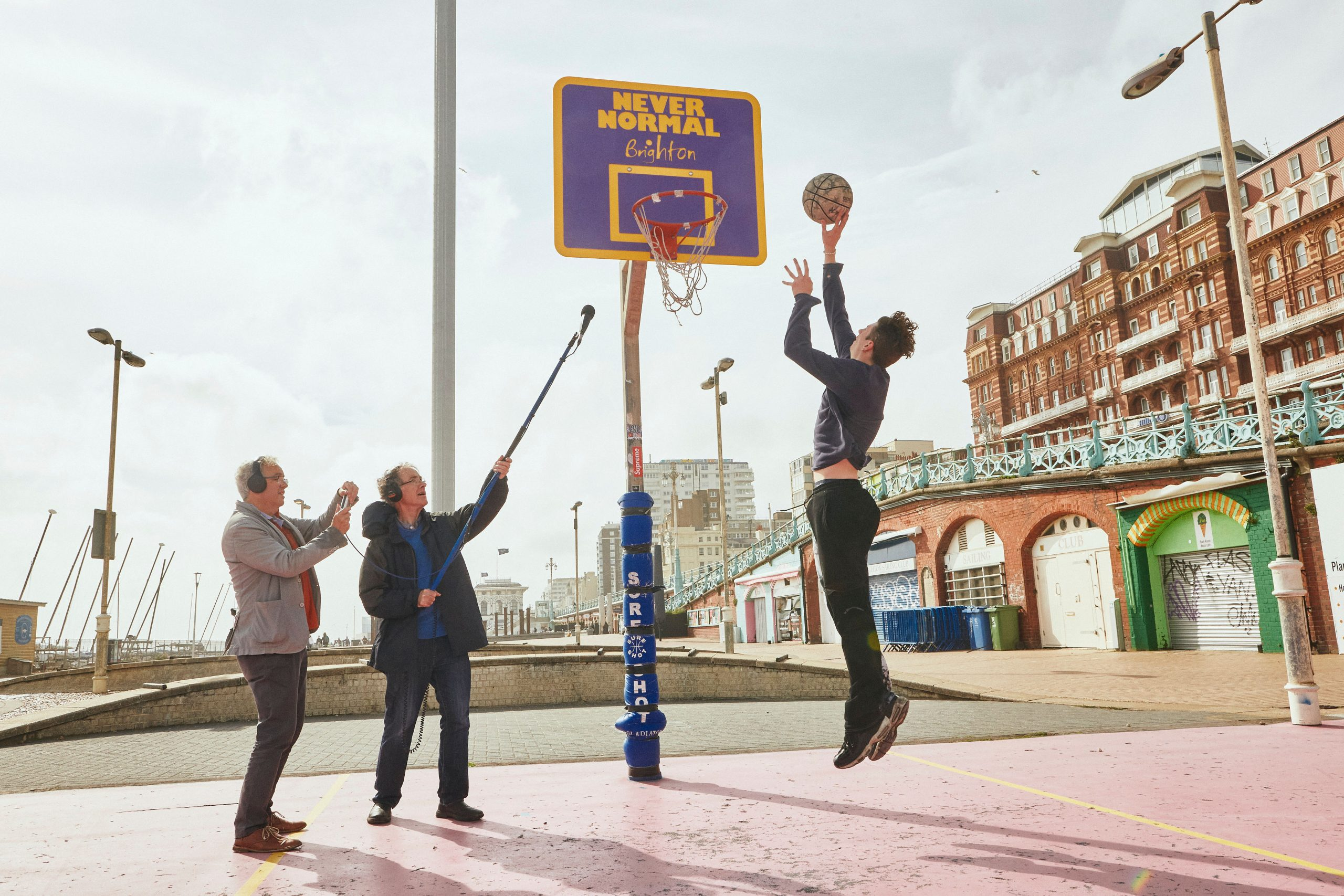 Man jumping in the air about to dunk a basketball into the net, on the right are two men one of which is holding up a microphone recording the sounds