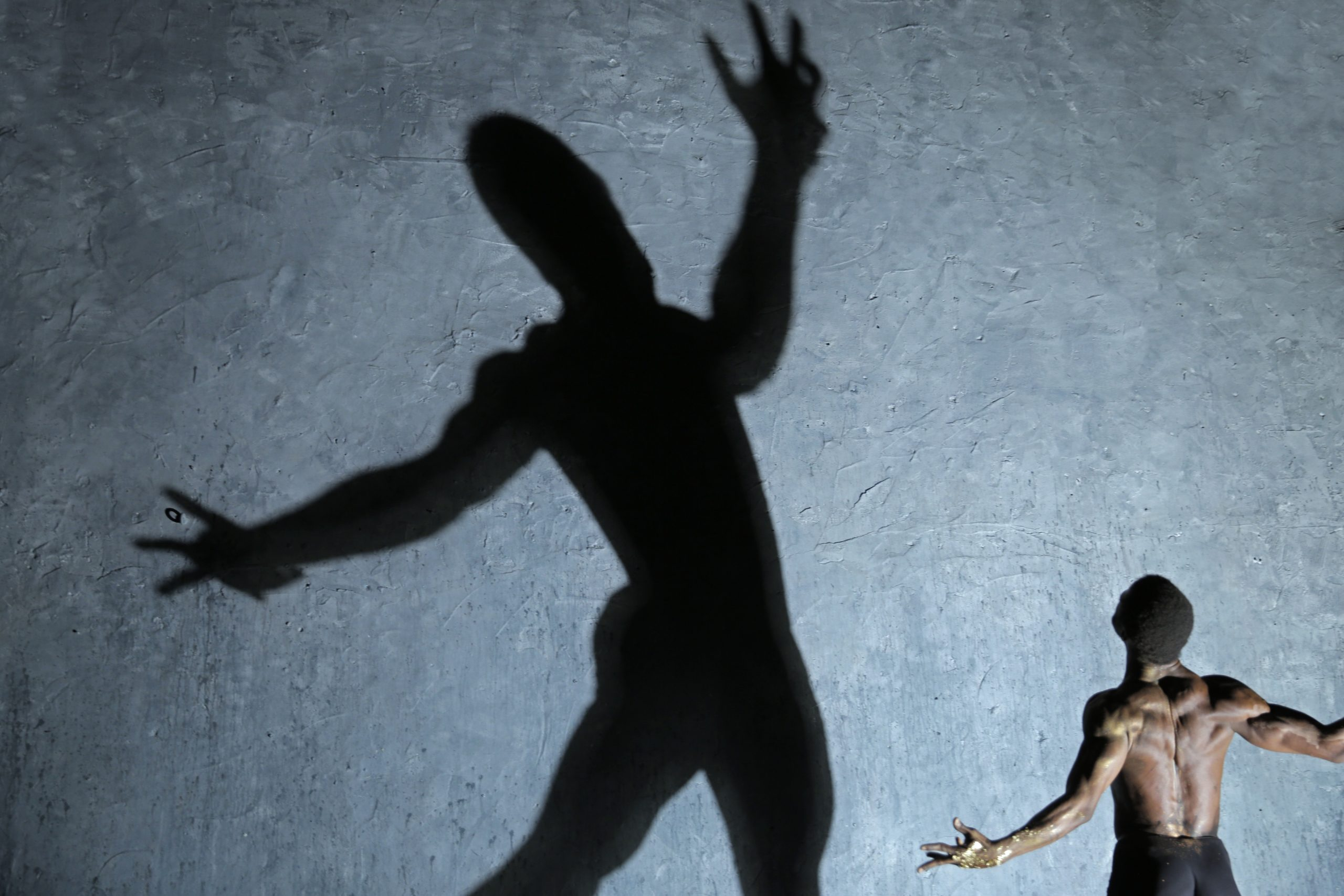 Man facing away and standing with his arms wide open - there is a giant shadow of him that is at the centre of the image