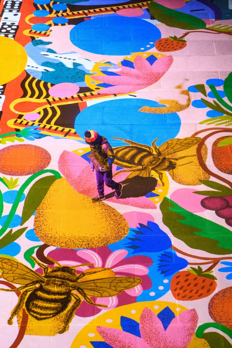 Child walking across multilcoloured floor projection with images of flowers, shapes, fruits and bees