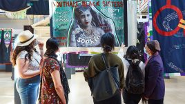 Southall Black Sisters looking at their banner at the Women Making History exhibition