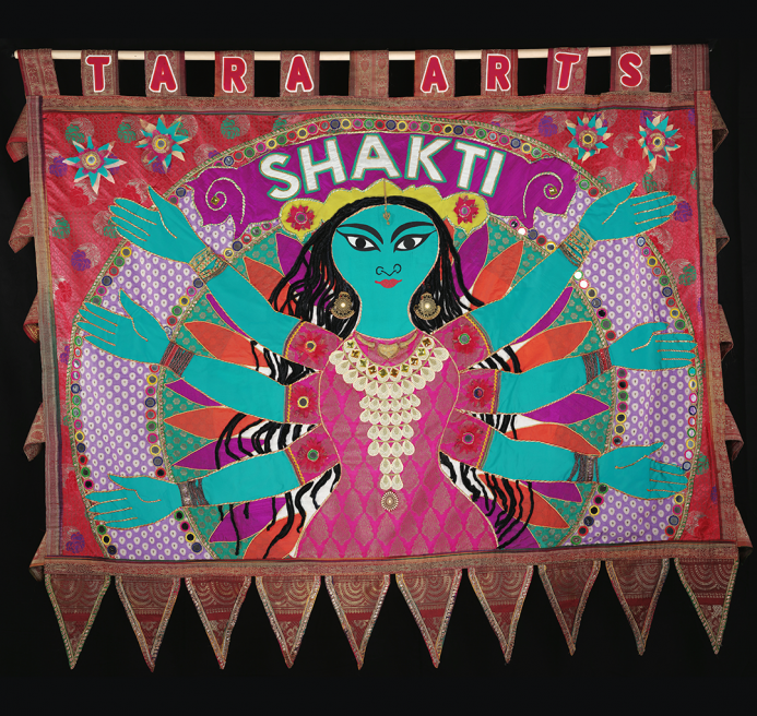 Blue human figure with 6 arms against pink and orange background made from recycled saris. SHAKTI is written above its head.