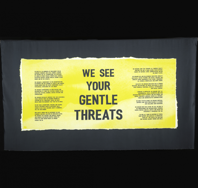 """A yellow banner, at the centre are the words """"WE SEE YOUR GENTLE THREATS"""" On the banner is also the manifesto collectively writen by a group of women from South Wales who have encountered gender-based violence."""
