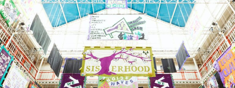 Below view of colourful banners with different messages around women's rights hanging in a brightly lit building