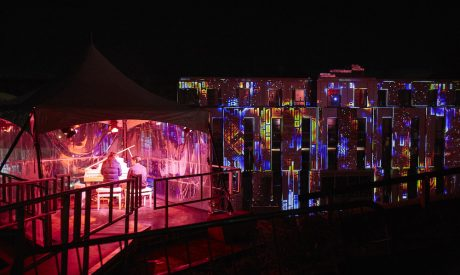Participants playing the piano to create a light multicoloured light projection on the building in front of them