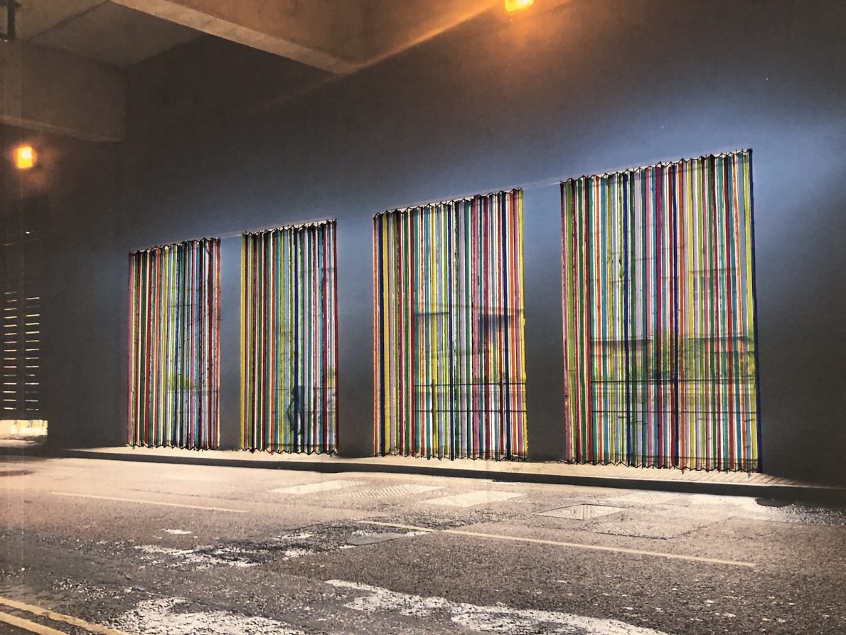 sketch of a rainbow of panels against a dark wall under a tunnel