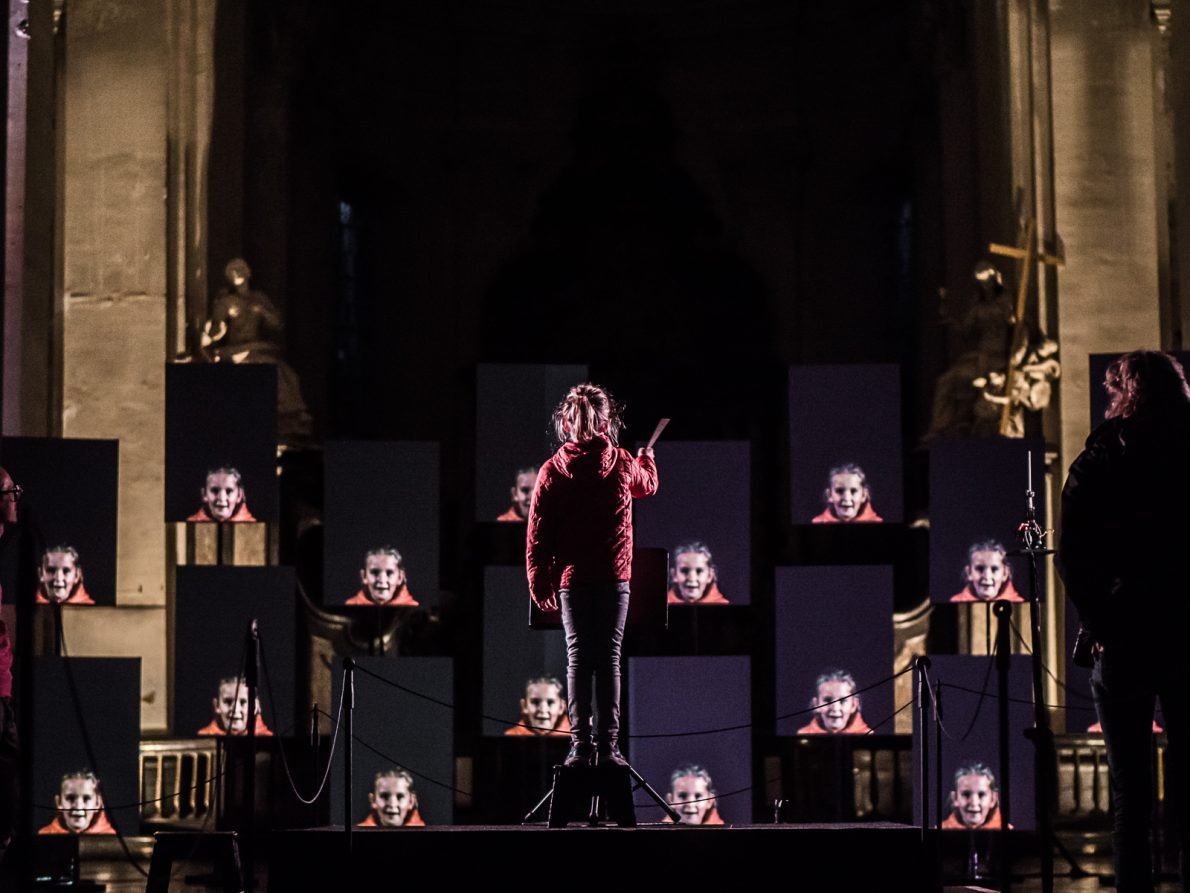 young girl stood up conducting and in front of her are multiple screens with an image of her face live